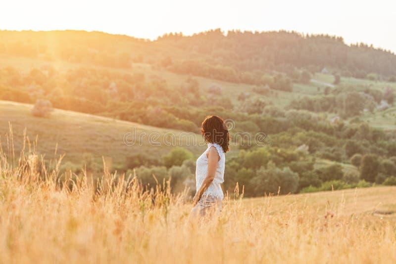 Härlig kvinnlig brunett för gullig lycklig romantiker på de gröna kullarna för sommar royaltyfri fotografi