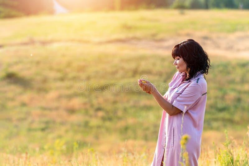 Härlig kvinnlig brunett för gullig lycklig romantiker på de gröna kullarna för sommar arkivbilder