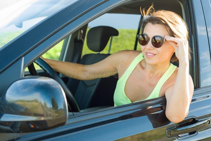 Härlig kvinnlig chaufför som ler, medan köra hennes bil royaltyfria bilder