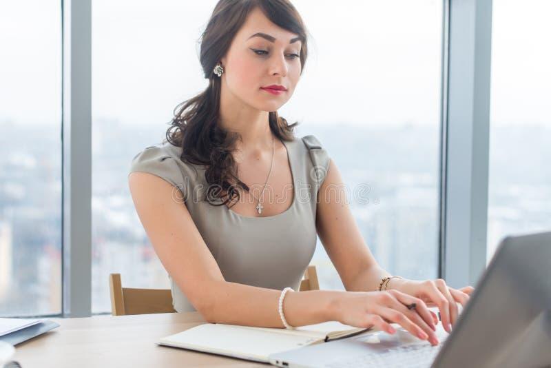 Härlig kvinnlig copywriter som i regeringsställning sitter och att skriva den nya artikeln och att arbeta med text, genom att anv royaltyfri foto