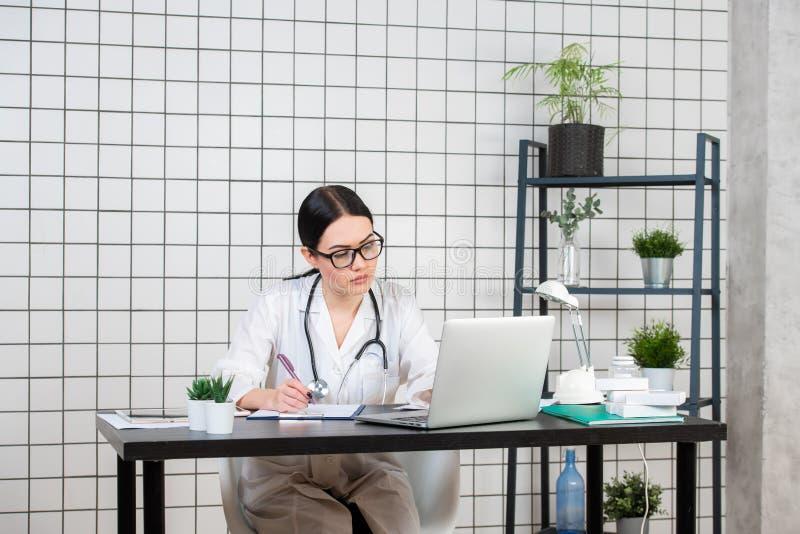 Härlig kvinnlig doktorshandstil, medan genom att använda bärbara datorn på skrivbordet i klinik royaltyfri foto