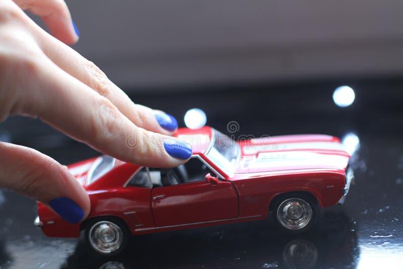 Härlig kvinnlig hand med manikyr och den röda retro leksakbilen Ljusa blått spikar polermedel fotografering för bildbyråer