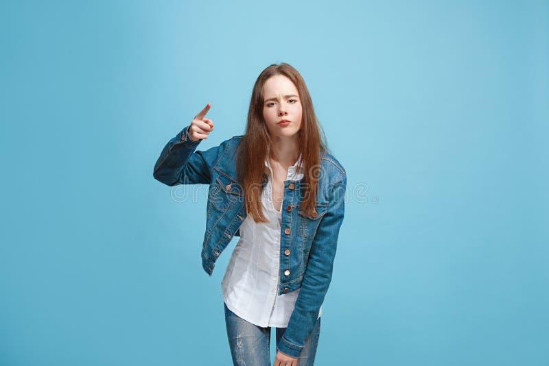 Härlig kvinnlig i halvfigur stående på blå studiobackgroud Den unga emotionella tonåriga flickan arkivbild