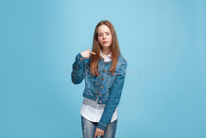 Härlig kvinnlig i halvfigur stående på blå studiobackgroud Den unga emotionella tonåriga flickan royaltyfria foton