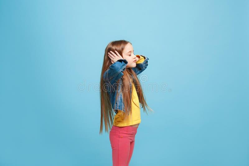 Härlig kvinnlig i halvfigur stående på blå studiobackgroud Den unga emotionella tonåriga flickan fotografering för bildbyråer