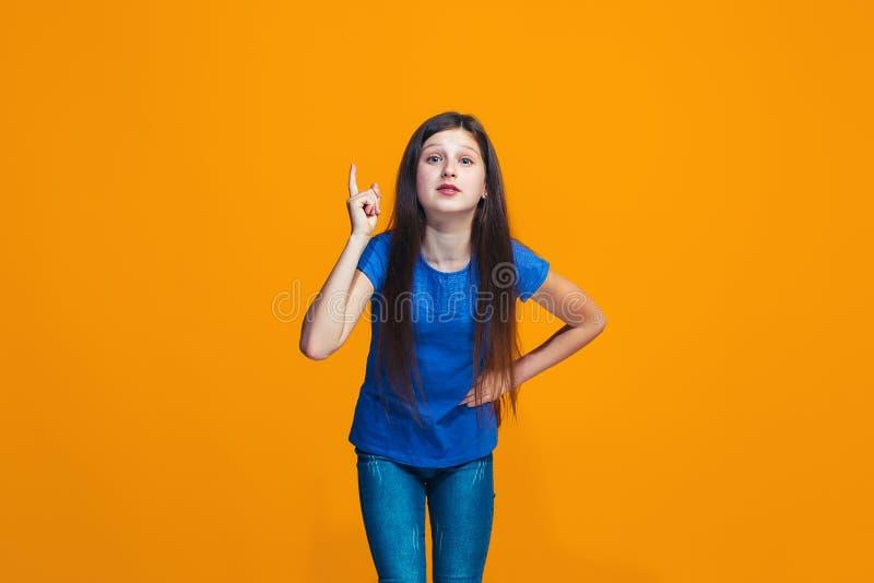 Härlig kvinnlig i halvfigur stående på orange studiobackgroud Den unga emotionella tonåriga flickan royaltyfria foton
