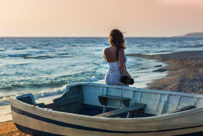 Härlig kvinnlig i pareoen nära fartyget på sanden royaltyfri fotografi