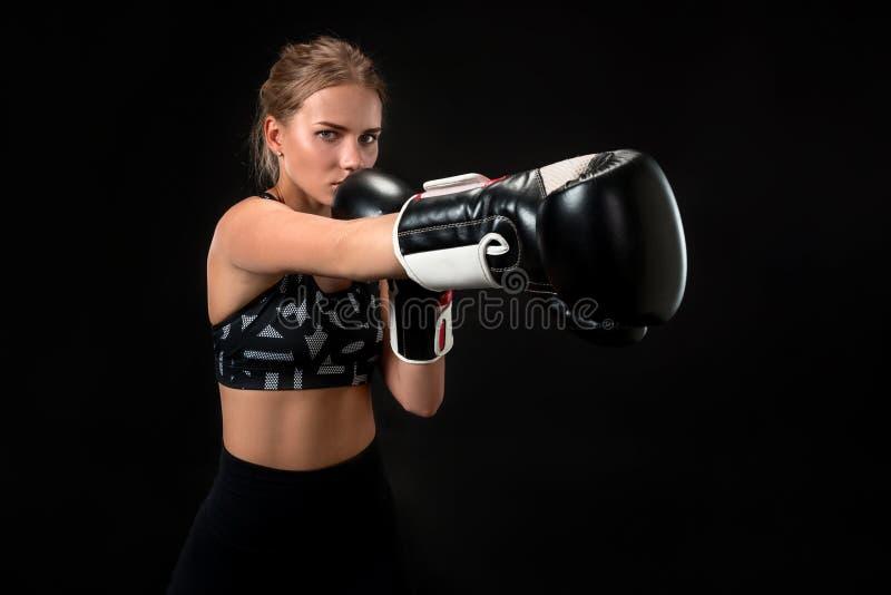 Härlig kvinnlig idrottsman nen i boxninghandskar, i studion på en svart bakgrund Fokus på handsken arkivbild