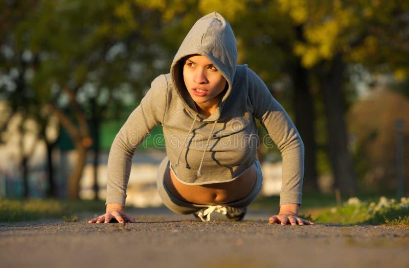 Härlig kvinnlig idrottsman nen som utomhus övar royaltyfri foto