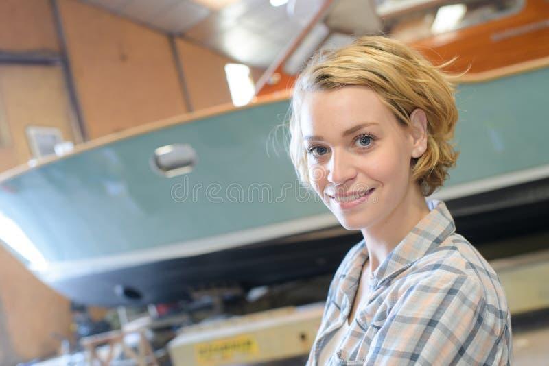 Härlig kvinnlig marin- byggmästare i skjul arkivfoton
