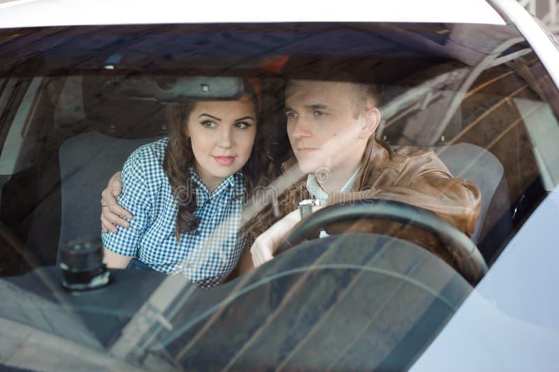 Härlig kvinnlig mekaniker med en stilig man i bilen fotografering för bildbyråer