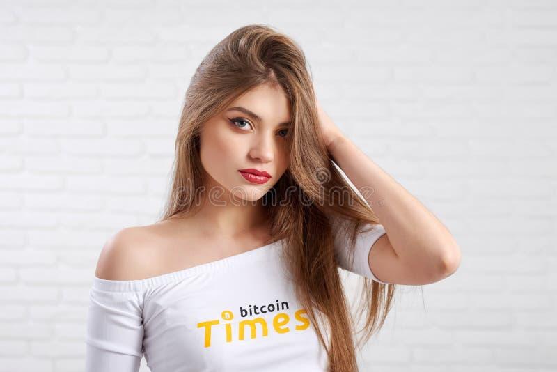 Härlig kvinnlig modell i den vita skördöverkanten med bitcoinlogoen som poserar till kameran royaltyfri fotografi