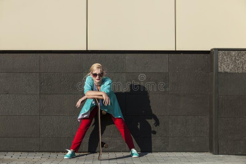 Härlig kvinnlig modell i tillfällig kläder med en skateboard arkivbilder