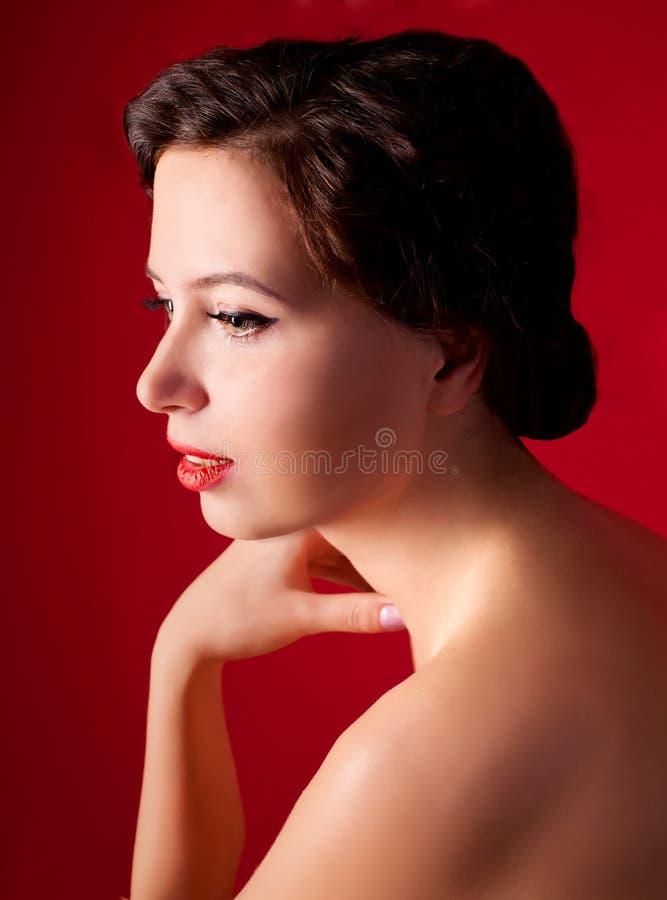 härlig kvinnlig modell på röd bakgrund royaltyfri bild
