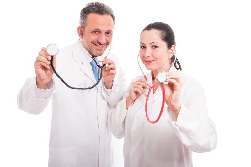 Härlig kvinnlig och manläkare med deras stetoskop royaltyfri fotografi