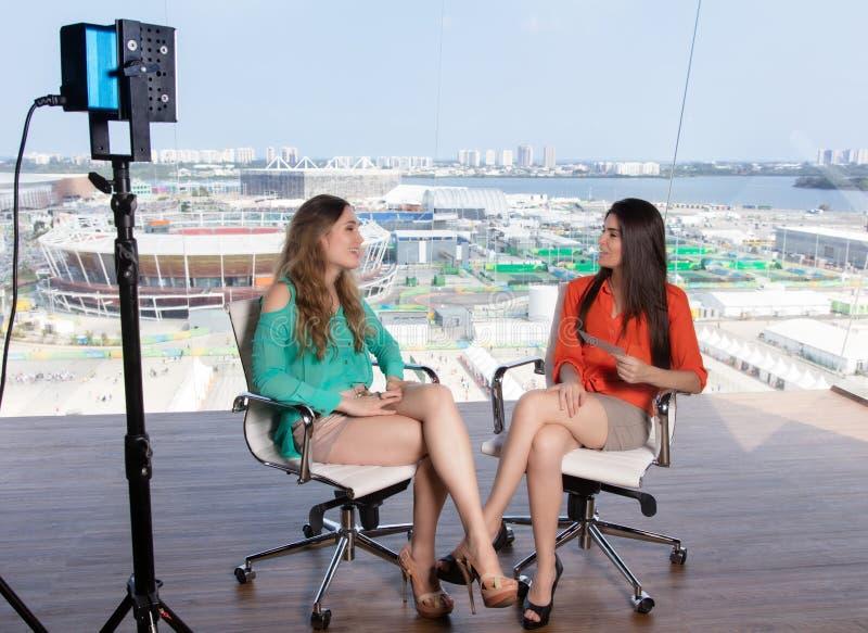 Härlig kvinnlig presentatör som intervjuar en berömd kvinna royaltyfria bilder