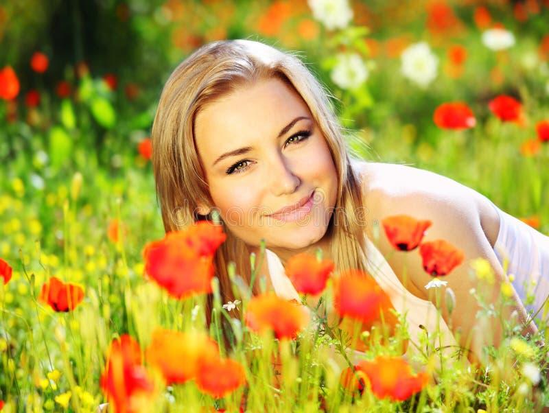 Härlig kvinnlig som lägger på den sparade blomman arkivbild