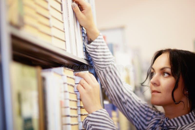 Härlig kvinnlig student In ett universitetarkiv royaltyfri foto