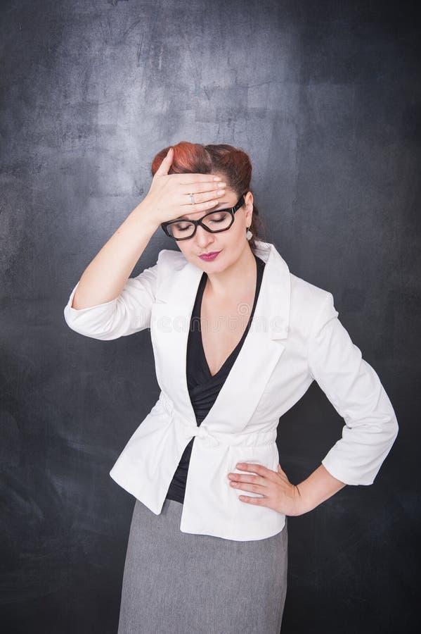 Härlig lärare med huvudvärk på svart tavlabakgrund arkivfoto