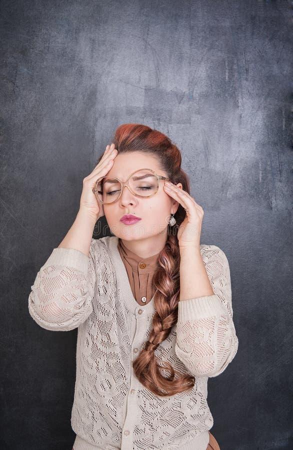 Härlig lärare med huvudvärk på svart tavlabakgrunden arkivbilder