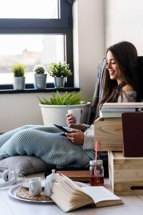 Härlig läs- eBookavläsare för ung kvinna hemma royaltyfri bild