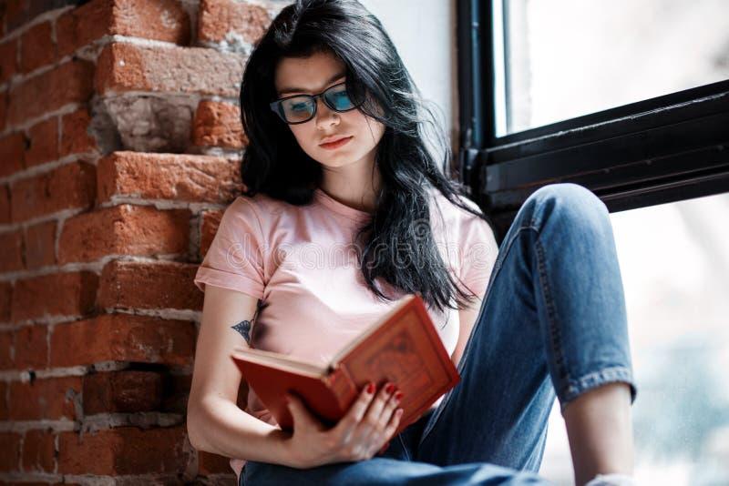 Härlig läsebok för ung kvinna för brunett vid fönstret hemma royaltyfri fotografi