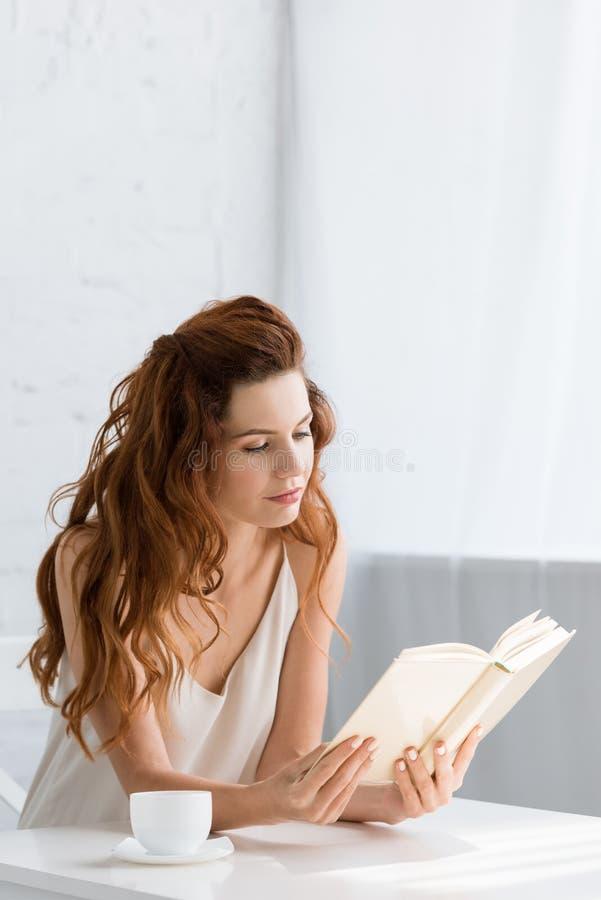 härlig läsebok för ung kvinna med kaffekoppen på tabellen arkivfoton