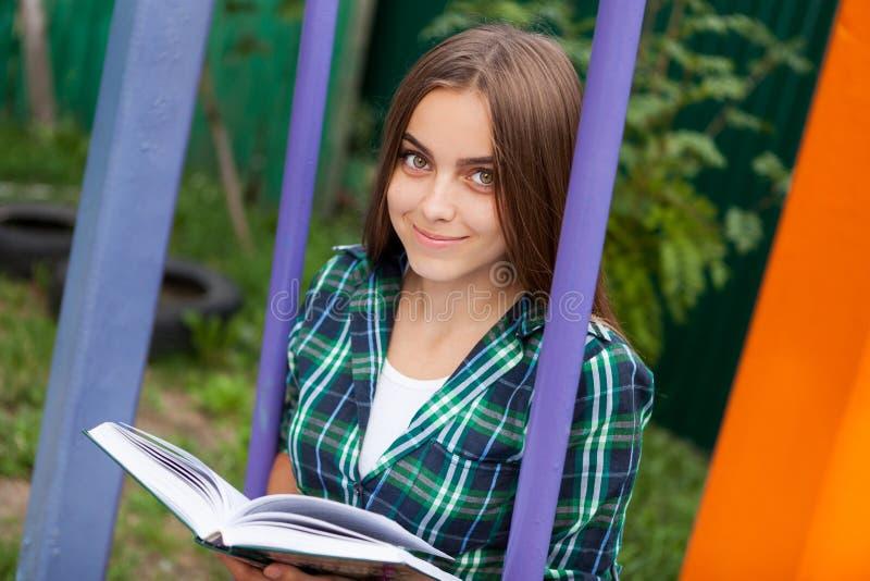Härlig läst bok för tonårs- flicka utomhus royaltyfri foto