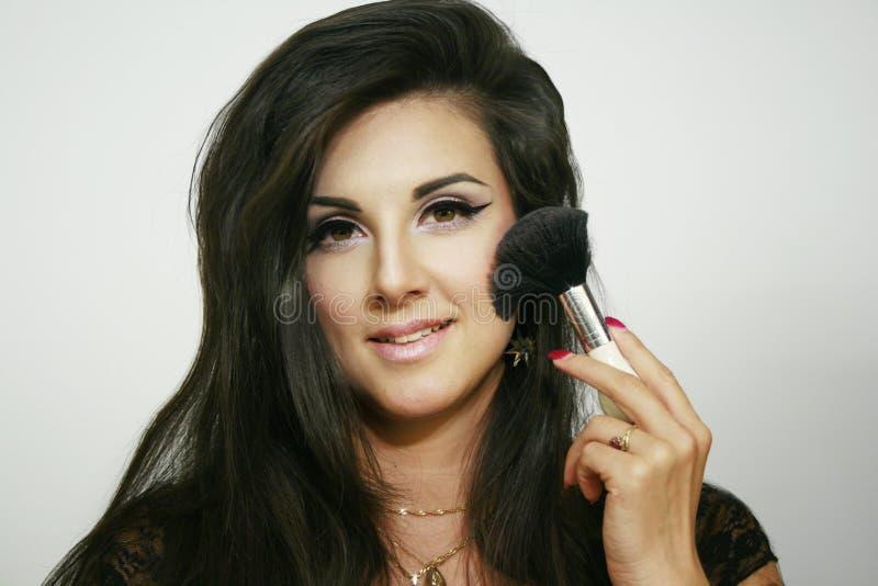 Härlig lång hårflicka, stor fluffig borste för kosmetiskt smileykvinnabruk på neutral bakgrund royaltyfri foto