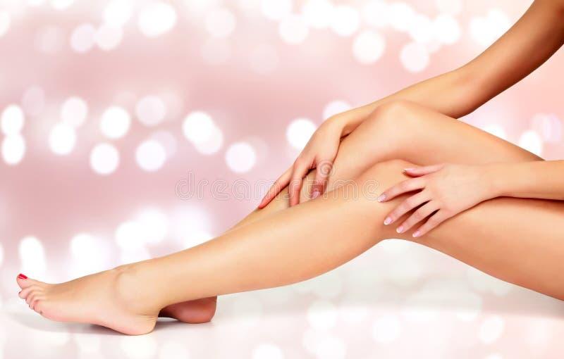 Härlig lång kvinna` s lägger benen på ryggen och händer med slät och mjuk hud royaltyfria foton