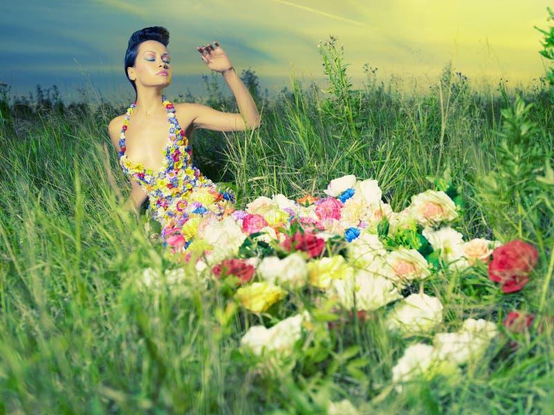 Härlig lady i klänning av blommor royaltyfria foton