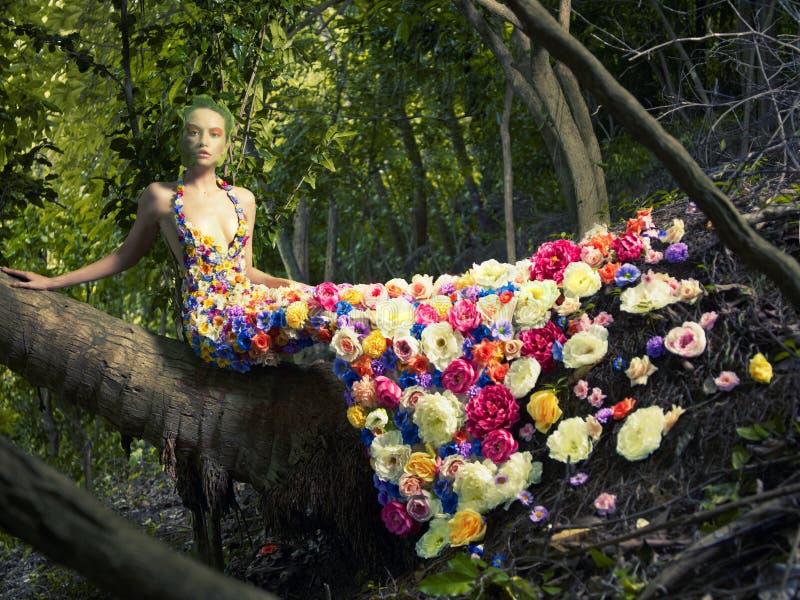 Härlig lady i klänning av blommor arkivfoton