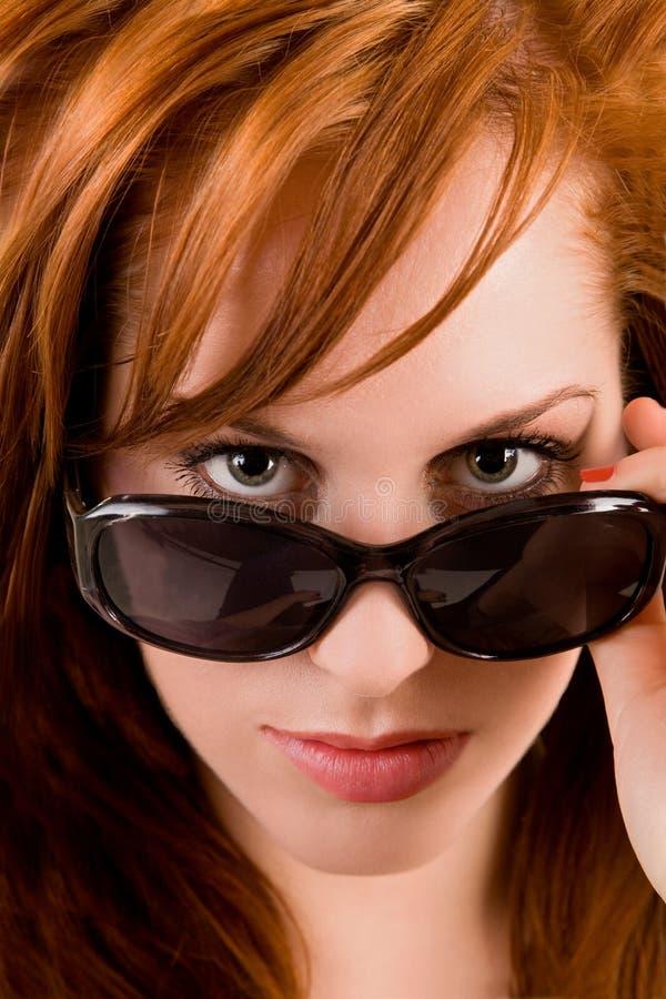 härlig lady som ser över redheadsolglasögon arkivbilder
