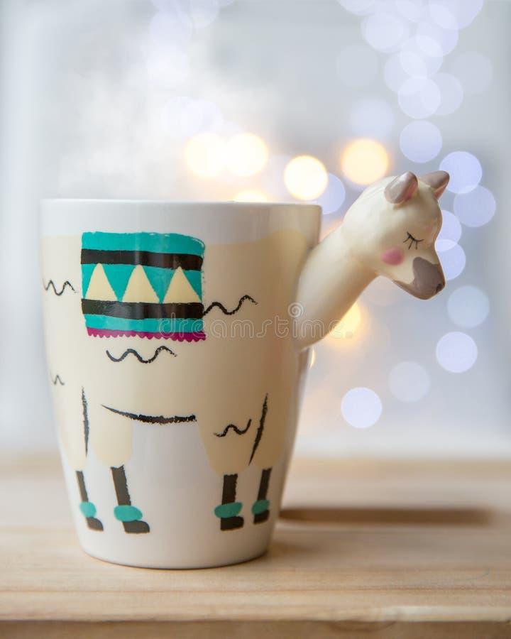 Härlig lama formad moderiktig kopp med varmt te med ljus på bakgrund Hemtrevligt höst-vinter begrepp royaltyfri fotografi