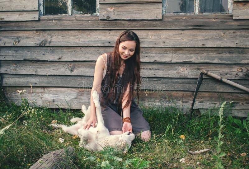 Härlig landsbohoflicka som spelar med en vit hund arkivbilder