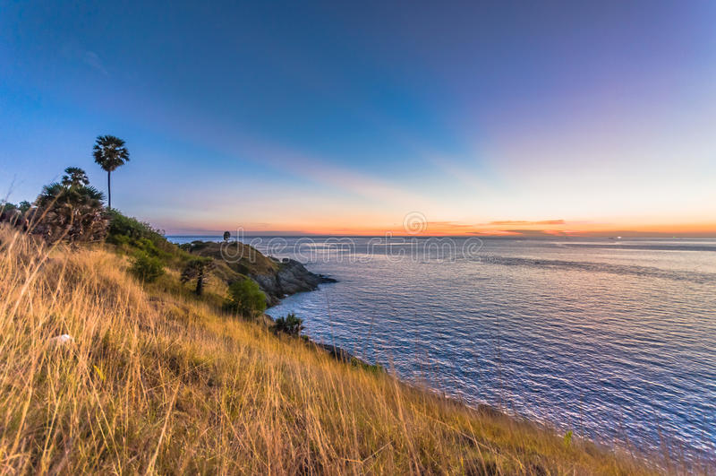 Härlig landskap och tropiskt Efter solnedgång och skymning över havet och udden med gult gräs och vagga uddeförgrund royaltyfria bilder