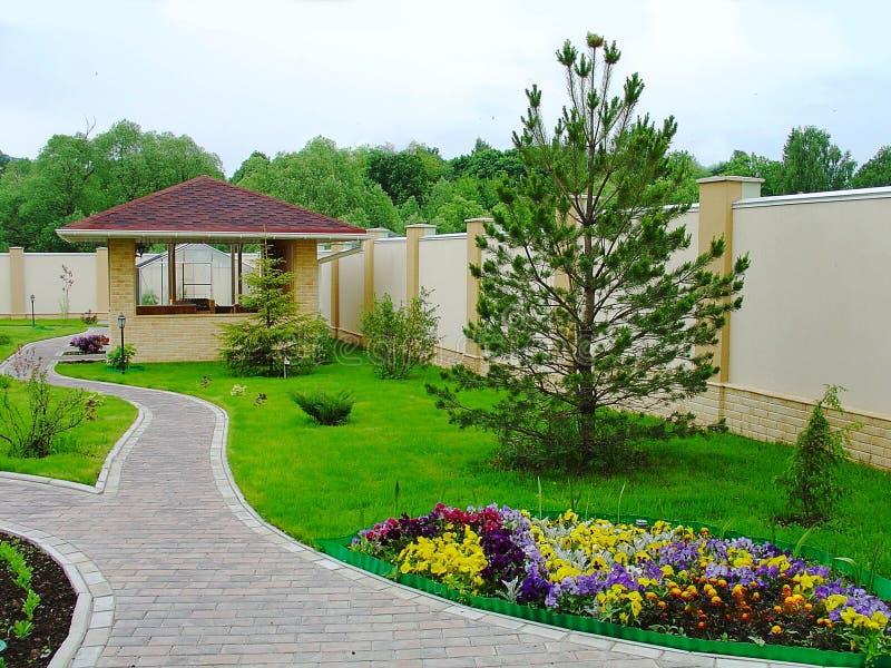 Härlig landskapdesign i en privat gård Färgrika blommor, grönt gräs och träd Mysigt grillfesthus/gallerhus Beautifu arkivbild