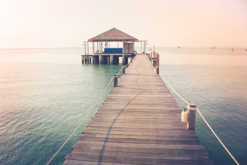Härlig landskapsikt av den långa träbron in i havet och paviljongen arkivfoton