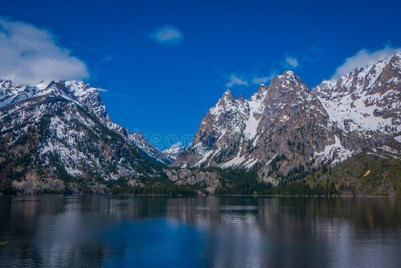 Härlig landskapsikt av det korkade berget för snö, storslagna Tetons som reflekterar på vatten fotografering för bildbyråer