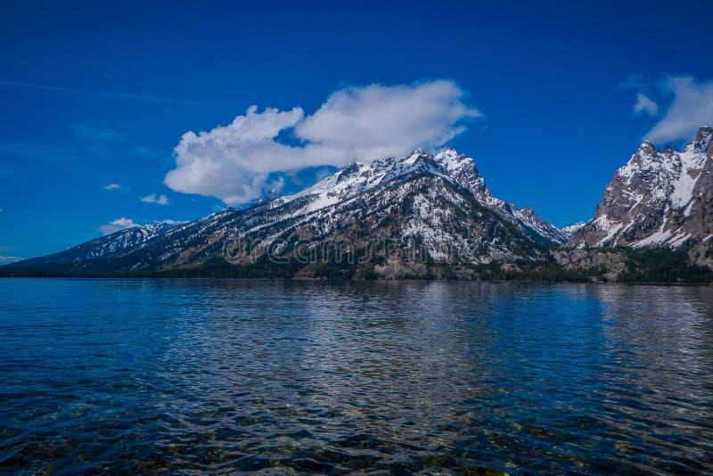 Härlig landskapsikt av det korkade berget för snö, storslagna Tetons som reflekterar på vatten arkivfoton