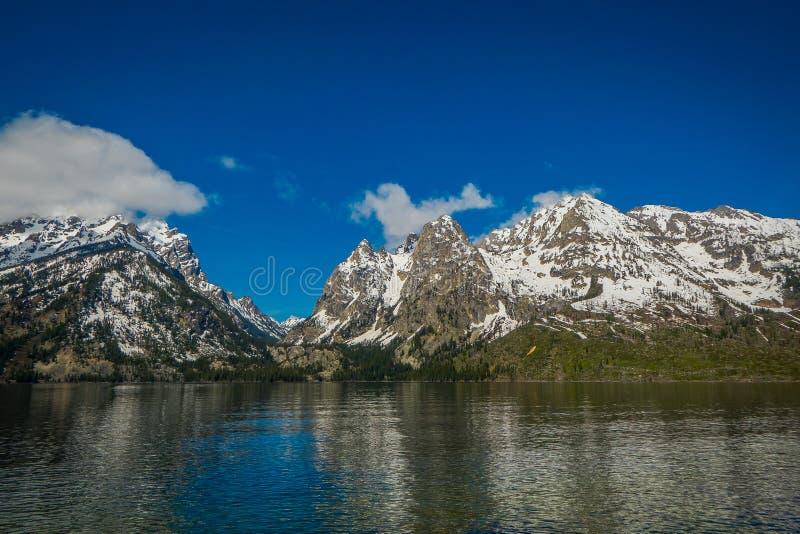 Härlig landskapsikt av det korkade berget för snö, storslagna Tetons som reflekterar på vatten royaltyfria foton