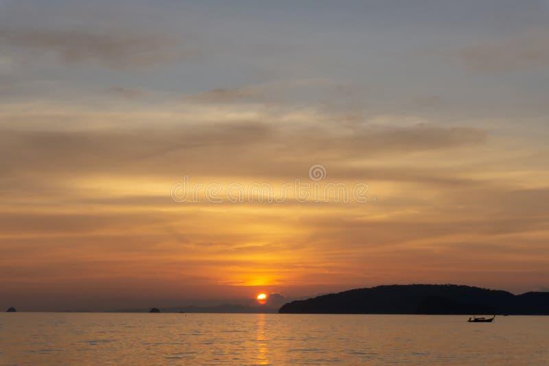 H?rlig landskapsolnedg?ng med gl?dande orange ljus som m?las p? molnig himmel som blis till skymninggryning, ovanf?r havet, farty arkivfoton