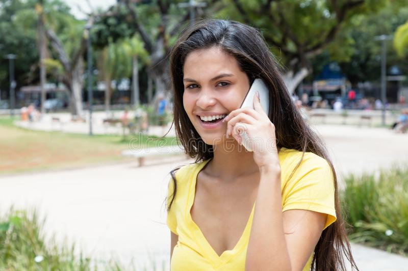 Härlig latin - amerikansk kvinna i gul skjorta på telefonen fotografering för bildbyråer