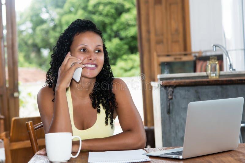 Härlig latin - amerikansk kvinna med svart hår på telefonen arkivfoton