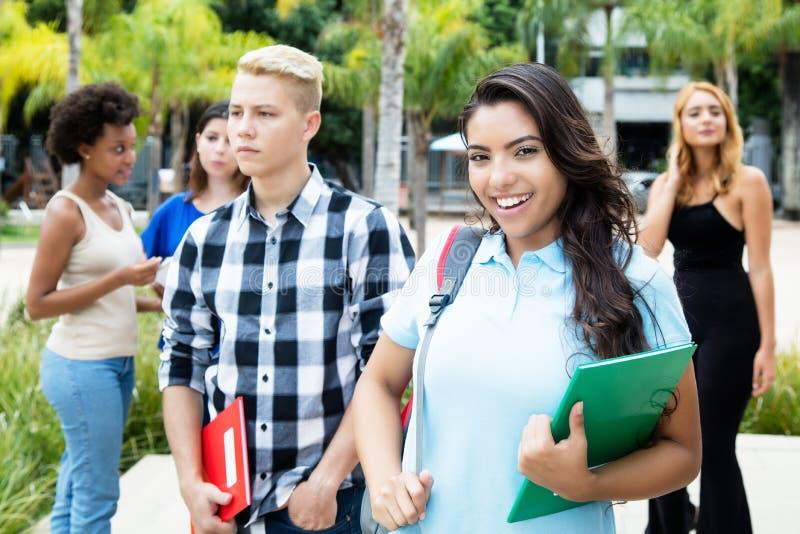 Härlig latin - amerikansk kvinnlig student med gruppen av internatio royaltyfri bild