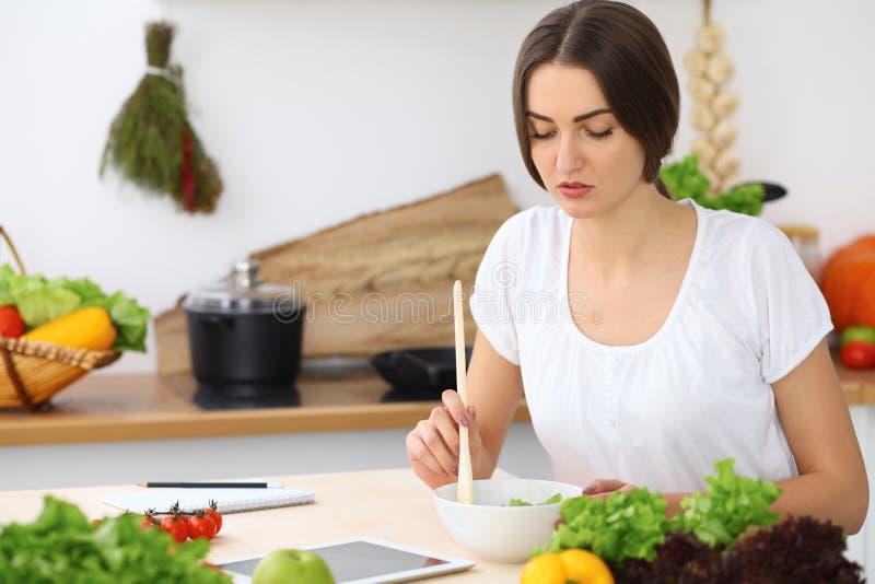 Härlig latinamerikan eller latin - den amerikanska kvinnan är den hållande träskeden, medan laga mat i köket royaltyfria bilder