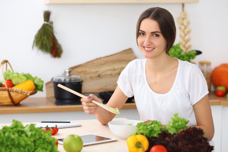 Härlig latinamerikan eller latin - den amerikanska kvinnan är den hållande träskeden, medan laga mat i köket arkivbilder