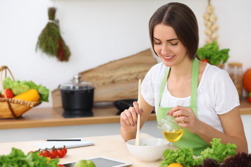 Härlig latinamerikan eller latin - den amerikanska kvinnan är den hållande träskeden, medan laga mat i köket arkivfoton