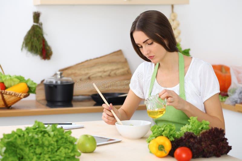 Härlig latinamerikan eller latin - den amerikanska kvinnan är den hållande träskeden, medan laga mat i köket royaltyfri foto
