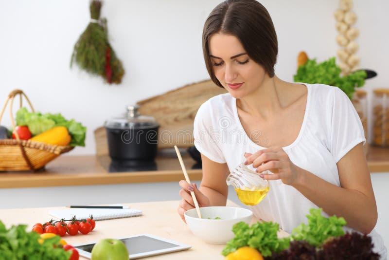 Härlig latinamerikan eller latin - den amerikanska kvinnan är den hållande träskeden, medan laga mat i köket royaltyfri bild